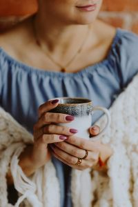Kaboompics - A woman in a warm blanket holds a cup of coffee or tea