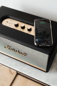 Kaboompics - Black speaker on marble table, white wall, mobile phone
