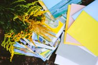 Kaboompics - Yellow flowers with postcards and colourful envelopes