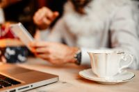 Kaboompics - The designer sits at his desk and drinks coffee using his phone & laptop