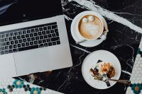 Kaboompics - MacBook laptop, coffee and cake with meringue and whipped cream on black marble