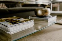 Kaboompics - Stack of magazines on the glass coffee table