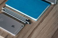 Silver iPhone with a blue notebook and pencils
