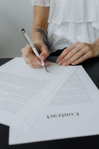 A businesswoman signs a contract