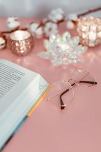 Kaboompics - An open book, candles and glasses on a pink background