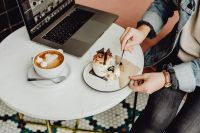 Kaboompics - Working with a laptop, meringue with whipped cream and coffee on white marble