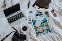 Kaboompics - Silver laptop, a camera, magazines and an iphone on white bed sheets
