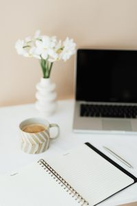 Laptop - white flowers - organizer & cup of coffee on marble table