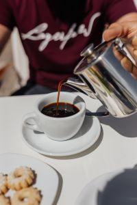 Kaboompics - Pouring coffee into a cup. Silver kettles, Italian cookies.