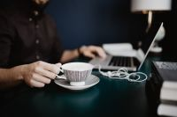 Male working with a laptop and a cup of coffee