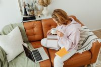 Kaboompics - Woman uses laptop - working from home - reading a book - writing in the planner