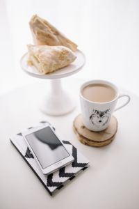 Black-and-white notebook and a white smarphone with various items