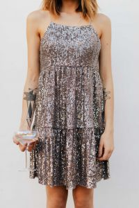 Kaboompics - Blond Woman in a Sequin Dress is Holding a Glass of Champagne, White Background