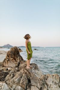 A woman in a green dress on a rock by the sea