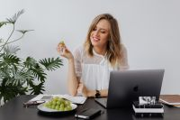 A businesswoman drinks coffee and eats grapes at work