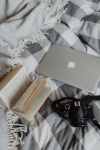 Kaboompics - A camera, MacBook, and a book waiting in bed