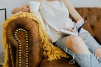 Kaboompics - Woman with a cup of coffee & book, yellow blanket, blue jeans pants, brown couch