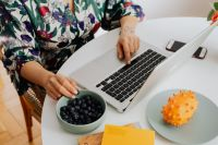 Woman, MacBook laptop, blueberries, kiwano fruit