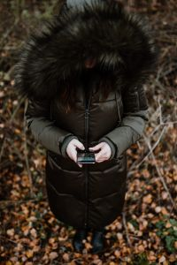 Kaboompics - A woman wearing a green winter jacket with a furry hood uses a phone