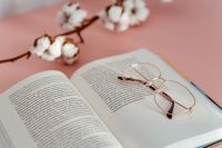 Kaboompics - An open book, glasses and a cotton branch on a pink background