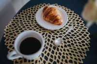 Kaboompics - Coffee cup with a croissant on a golden mat