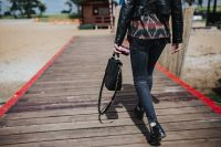 Kaboompics - Woman with a black bag and a can of coke walking on a wooden pier