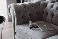 Kaboompics - Silver laptop and a magazine on a grey sofa