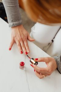 Closeup of a woman painting her nails with red nail polish