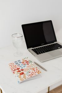 Laptop - organizer - glass of water & pen on marble table