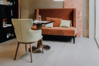 Kaboompics - Table between chair and orange sofa in floral living room or restaurant