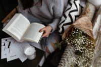 Kaboompics - A woman in a sweater reads a book