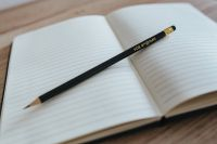 Kaboompics - Empty notebook with a black pencil on a wooden desk