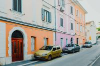 Kaboompics - Colourful tenement houses in Izola, Slovenia. Cars parked on the street.