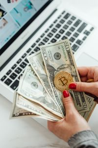 Kaboompics - The woman holds a Cryptocurrency Bitcoin & US Dollars