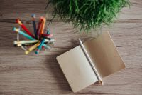 Small notebooks with colourful pencils in a jar on a wooden desk