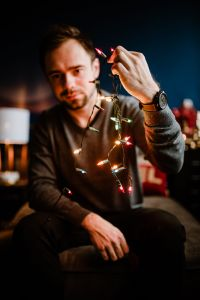 Kaboompics - A handsome young man with Christmas tree lamps