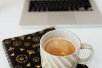 Laptop - organizer & cup of coffee on marble table