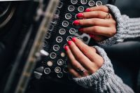 Kaboompics - Woman typing on an old typewriter