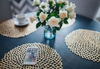 Kaboompics - Round breakfast table with golden coffee mats and white flowers