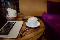 Kaboompics - Cup of coffee & MacBook laptop, glasses on table in cafe
