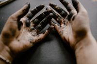 Messy painted hands of a painting artist