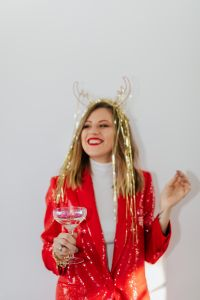 Kaboompics - Woman in a Red Jacket and Christmas Horns Celebrating New Year