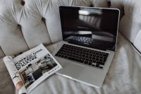 Kaboompics - Silver Apple MacBook Pro with a magazine on a bed