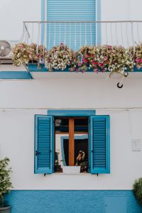 Kaboompics - White building with blue shutters and flowers on the balcony