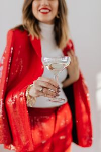 Kaboompics - Woman in red pants and a white shirt with champagne