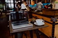 Kaboompics - Cup of coffee & MacBook laptop on table in cafe