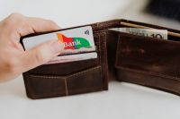 Kaboompics - Closeup man hand open brown genuine leather wallet with banknote and credit cards on marble background with clipping path