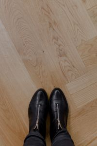 Kaboompics - The woman in black leather shoes is standing on the oak floor