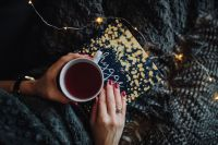 Kaboompics - Young woman at home reading Hygge book and drinking tea