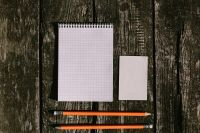 White notepad with pencils on a wooden background